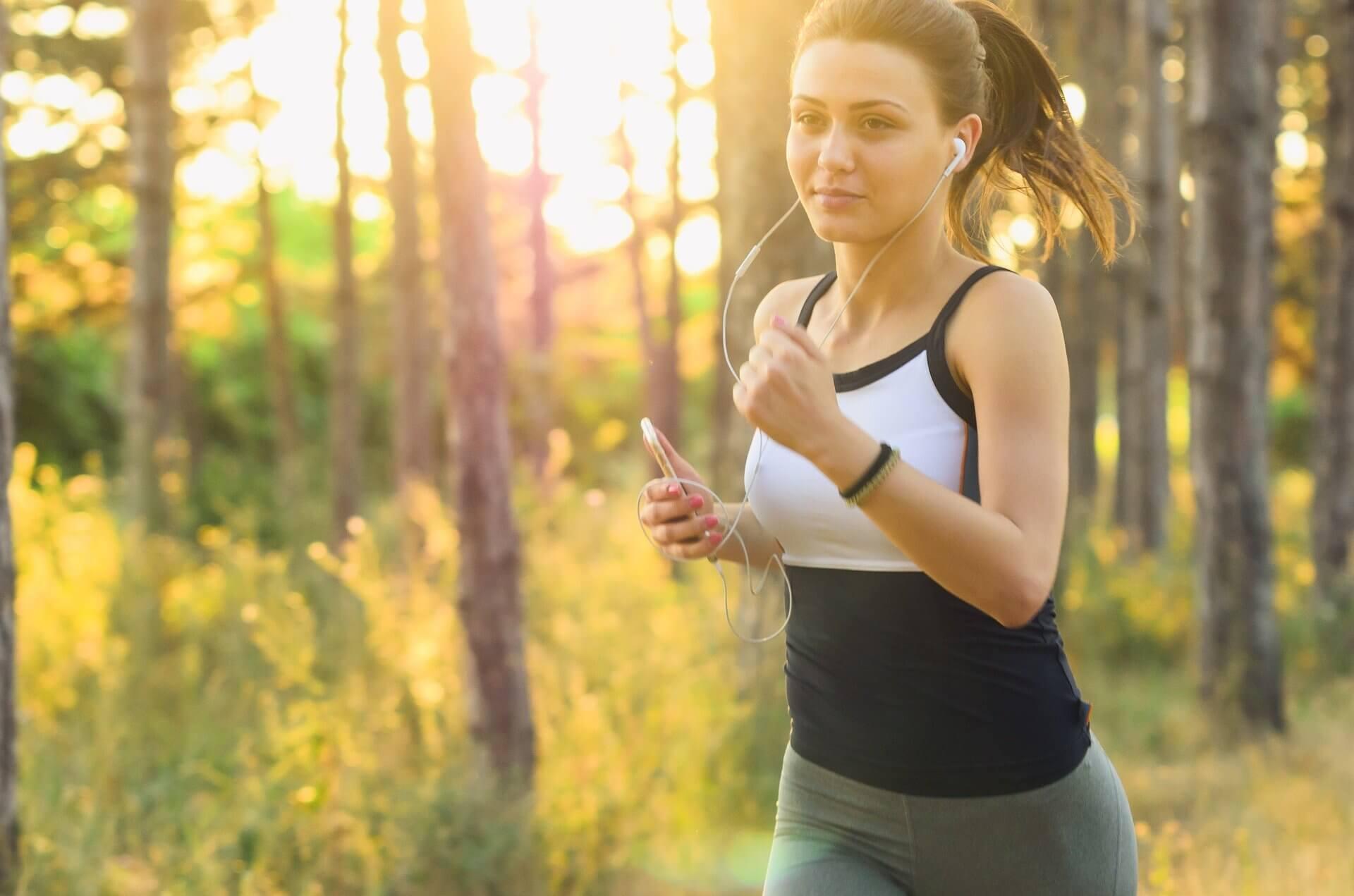 Kvinna som joggar i skogen.